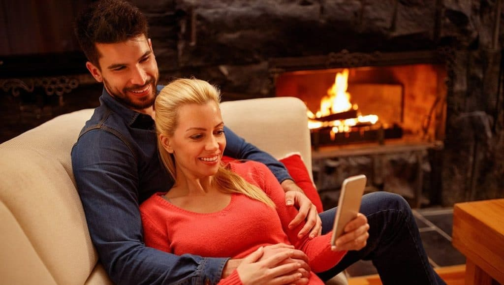 Couple on couch by wood fire image on safe home fireplace website
